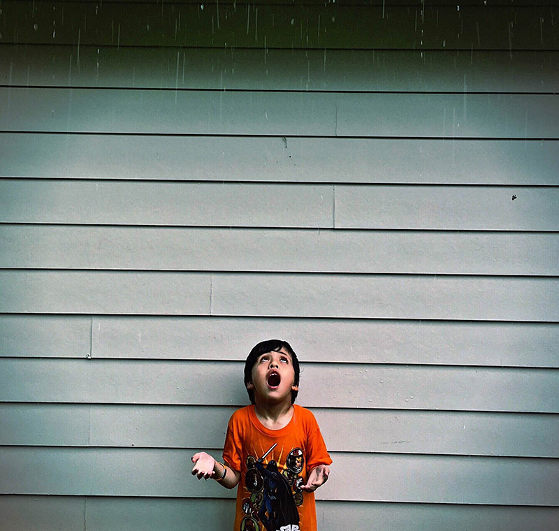 child standing in the rain